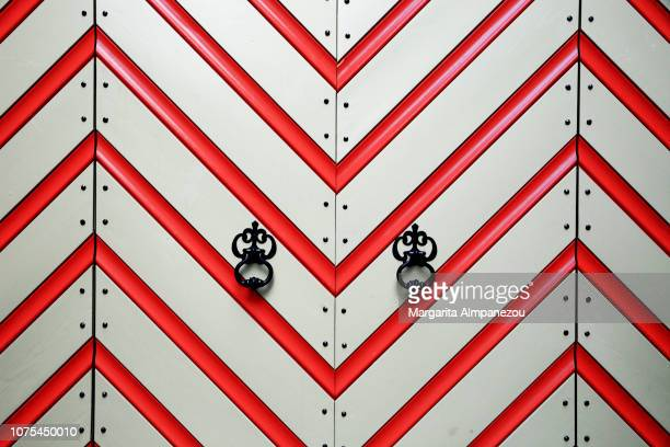 Perfect symmetry of red and white diagonal lines and handles on a door