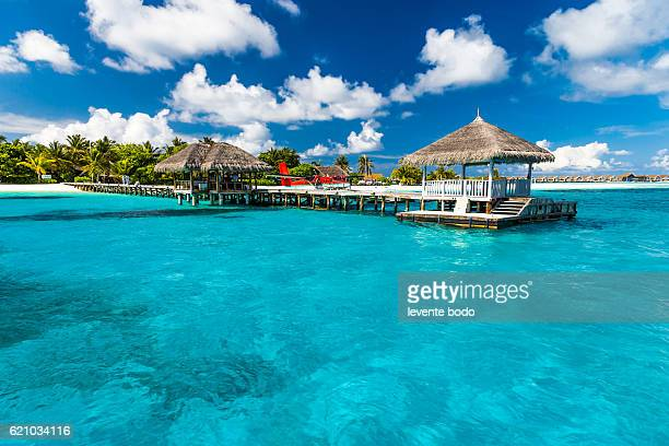Perfect tropical island paradise beach Maldives. Long jetty and a traditional boat dhoni.