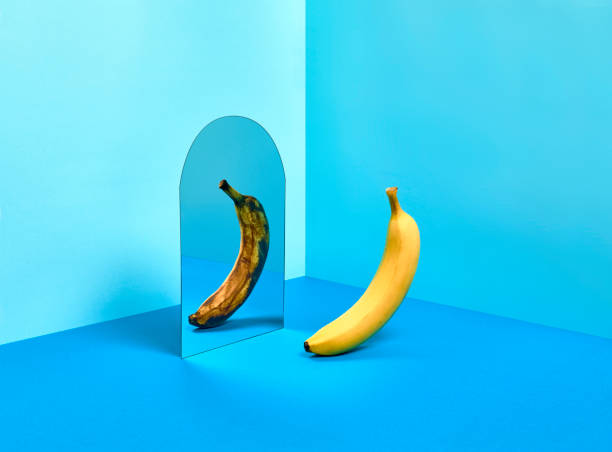 A perfect yellow banana reflecting a very mature image of herself in a mirror.