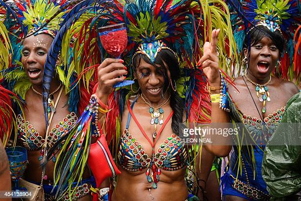 Perfomers dance during the second day of the Notting Hill Carnival in west London on August 25 2014 Heavy rain continued throughout the day dampening...