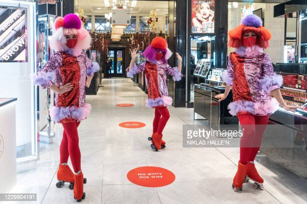 Perfomers on rollerskates wait to greet customers as the Selfridges department store reopens for general retail in London on December 2, 2020 as...
