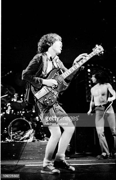 Perform on stage at the Lyceum, London, July 1976, L-R Angus Young, Bon Scott.