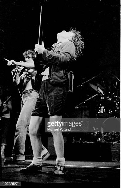 Perform on stage at the Lyceum, London, July 1976, L-R Bon Scott, Angus Young.