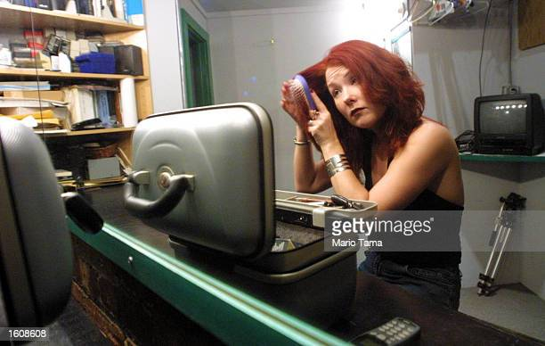 Performance artist and lap dancer Cathy MacGregor combs her hair in her dressing room August 11 2001 in New York City MacGregor who holds a PhD in...