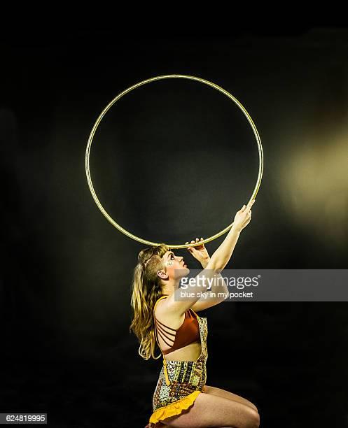 A performance artist balancing a hoop
