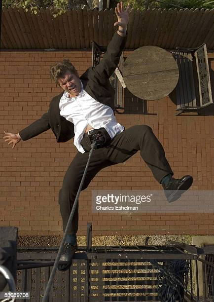 Performance artist Kerry Skarbakka 34yearsold gestures as he hangs from his fire escape by rope and harness at his studio May 14 2005 in the Brooklyn...