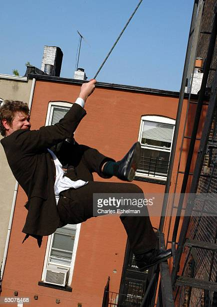 Performance artist Kerry Skarbakka 34yearsold prepares to hang from his fire escape by rope and harness at his studio May 14 2005 in the Brooklyn...