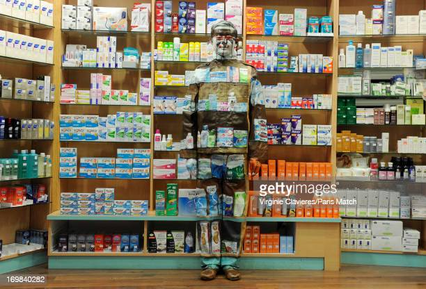 Performance artist Liu Bolin is photographed for Paris Match during preparation for a work which takes place at a pharmacist's and is a commentary on...