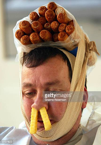 Performance artist Mark McGowan sits in a bath full of baked beans with two chips stuck up his nose and sausages strapped to his head in the window...
