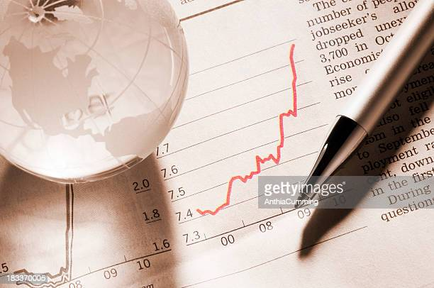 Performance graph in newspaper with pen and world globe