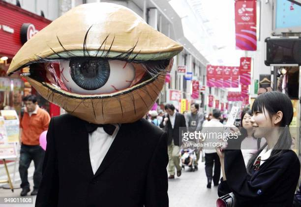 A performance group 'MedamanMedaman' or 'Eyeball Man' street performer covered with the mask of the big eyeball parades around a shopping district in...