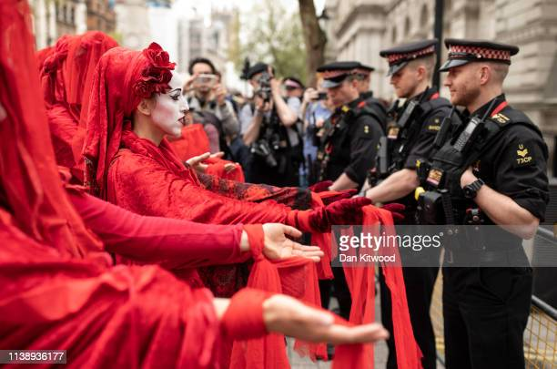 Performance group stage a silent demonstration outside Downing Street as Extinction Rebellion campaigners gather in Parliament Square on April 23,...