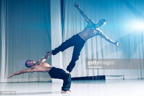 Performance indoor by two strong and muscular acrobats