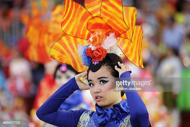 Performer adjusts her props as she dances down the street during the Chingay SG50 National Education Show at the F1 Pit Building on February 14, 2015...