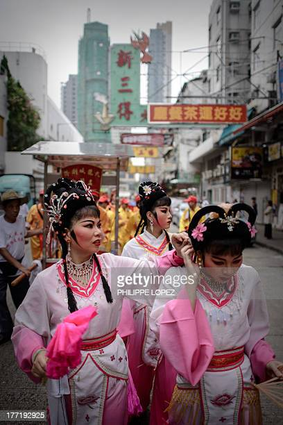 A performer arranges the hair of another during a parade for the Hungry Ghost Festival in Hong Kong on August 22 2013 The festival celebrated in the...