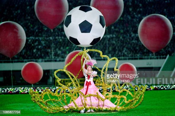 A performer dances beneath a balloon designed in the pattern of a soccer ball during the opening ceremony on November 16 in Guangzhou of the 1st FIFA...