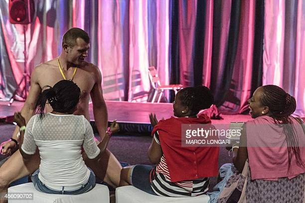 A performer dances for a group of South African women at the 2014 edition of the Sexpo in Midrand on September 25 2014 The health sexuality and...