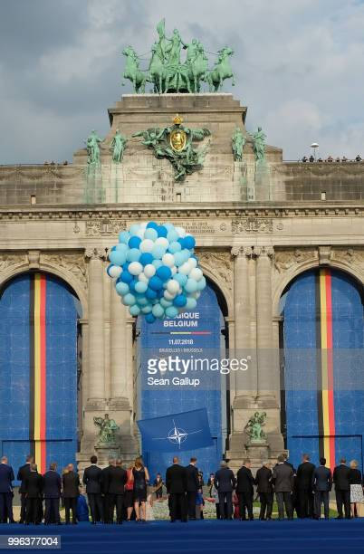 A performer dances suspended from balloons as heads of state and governments as well as their spouses watch at the evening reception and dinner at...