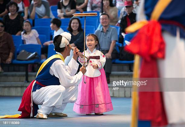 A performer demonstrates an acrobatic performance of 'Beona' a Korean traditional dishturning display for a young girl at a Seoul yard designed for...