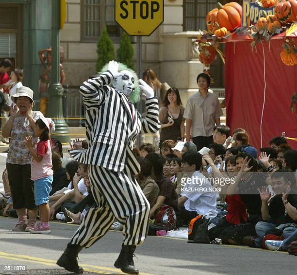 A performer disguised as movie character Beetlejuice Haunted Beat performs in a dancing parade at Osaka's Universal Studios Japan 16 September 2003...