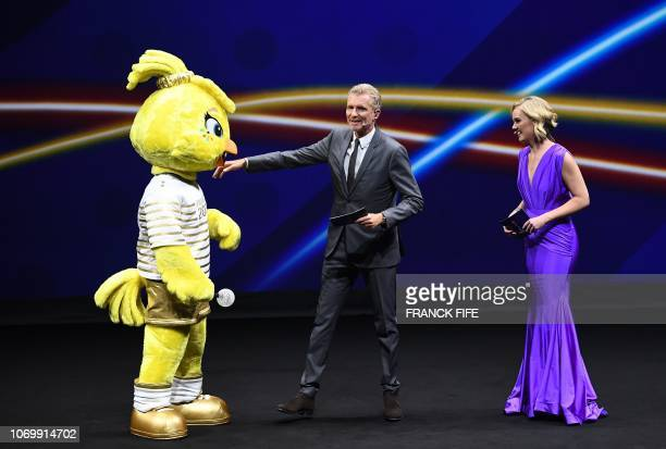 A performer dressed as 2019 FIFA mascot Ettie French Sports journalist Denis Brogniart and Sports TV host for CNN International Amanda Davies attend...