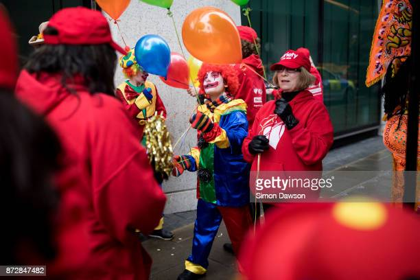 A performer dressed as a clown looks at a balloon before marching in the Lord Mayor's Show on November 11 2017 in London England The Lord Mayor's...