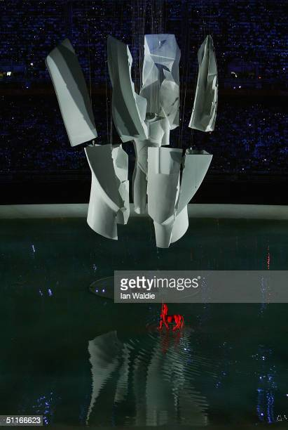A performer dressed as a mytholgical Centaur throws a symbolic javelin as a giant white Cycladic head rises from the water and breaks apart during...