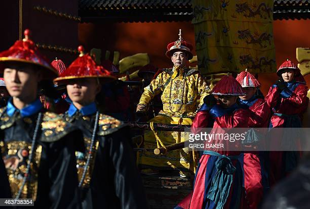 A performer dressed as a Qing Dynasty emperor is carried in a sedan chair during a recreation of a sacrifice ceremony at Ditan Park or the Altar of...