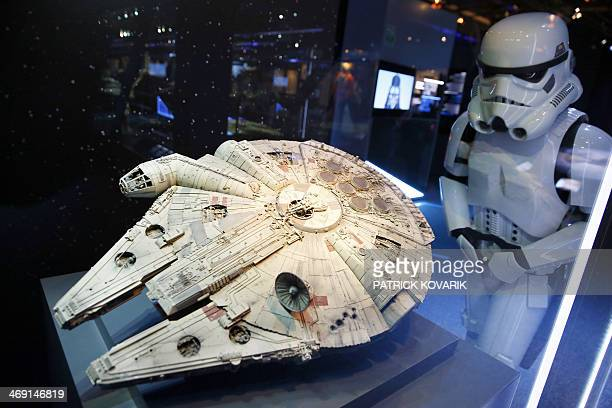 A performer dressed as a stormtrooper character looks at a model of the Millenium Falcon starship from the Star Wars film series displayed during the...