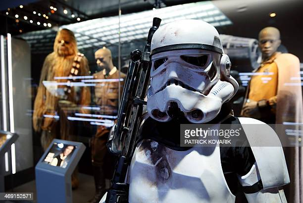 Performer dressed as a stormtrooper from the Star Wars film series stands in front of costumes of characters Chewbacca and Han Solo, displayed during...