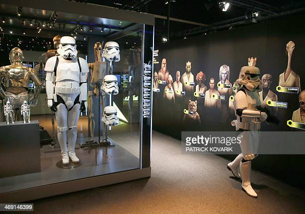 A performer dressed as a stormtrooper walks by as a costume and helmets of a stormtrooper character from the Star Wars film series are displayed...