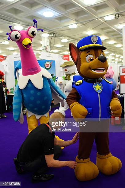 Performer dressed as Chase from the cartoon PAW Patrol has his costume adjusted ahead of the Brand Licensing Europe character parade at Olympia...