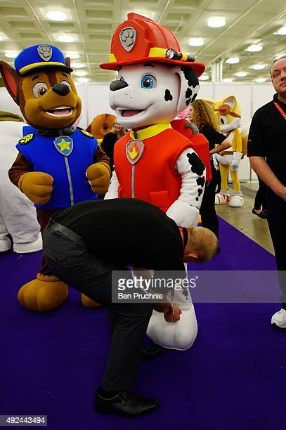 Performer dressed as Marshall from the cartoon PAW Patrol has his costume adjusted ahead of the Brand Licensing Europe character parade at Olympia...
