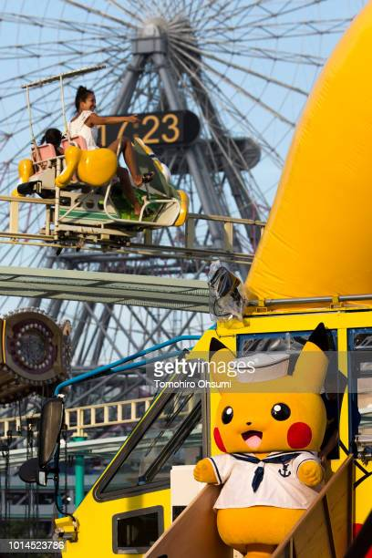 A performer dressed as Pikachu a character from Pokemon series game titles disembarks an amphibious bus as a woman rides a cycle monorail during the...