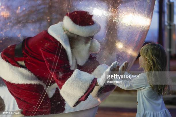 Performer dressed as Santa Claus greets a child from inside a bubble during the Lights on Broadway event in Oklahoma City, Oklahoma, U.S., on...