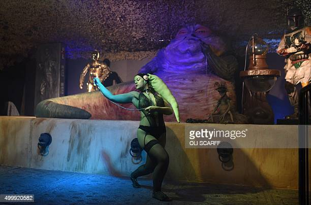 A performer dressed as the Star Wars character 'Oola' dances in front of an animatronic model of Jabba the Hutt during the unofficial Star Wars...