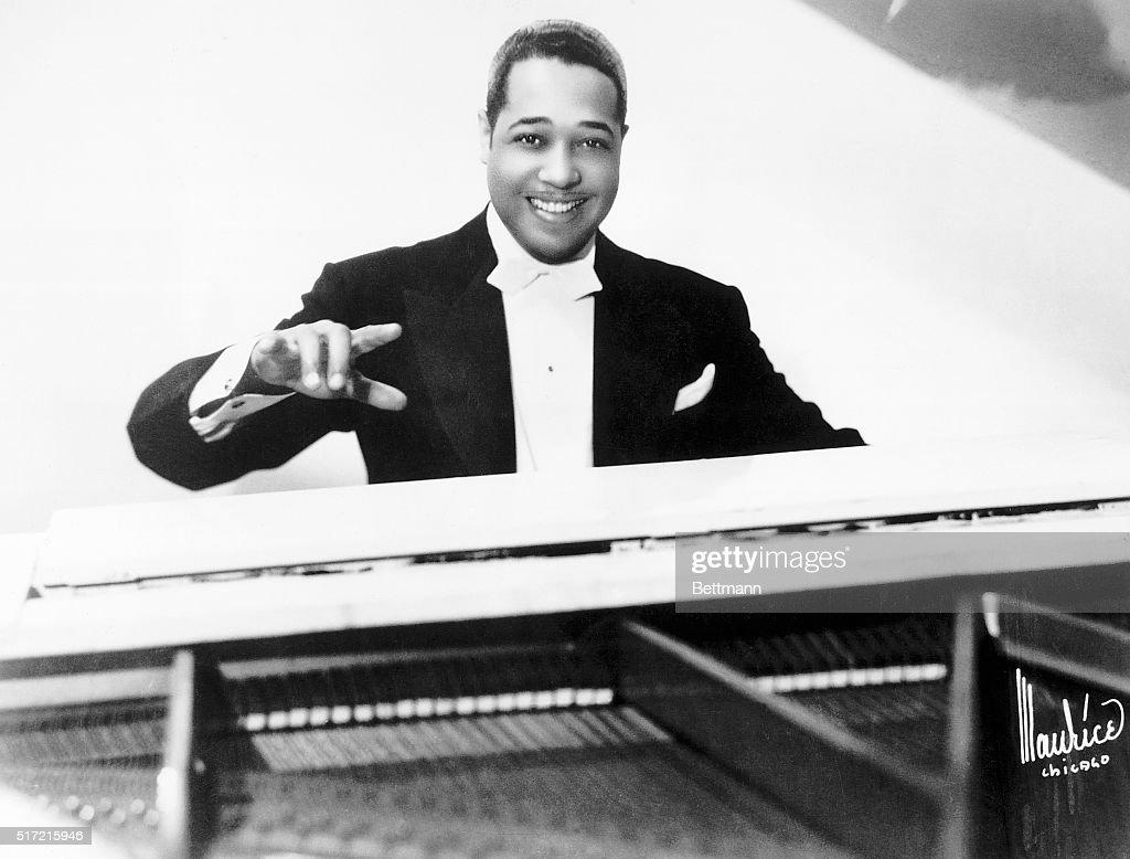 Performer Duke Ellington seated at a piano wearing a tuxedo.
