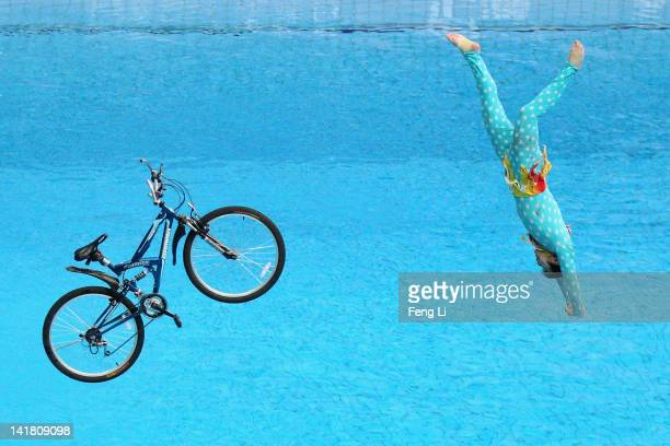 A performer falls with a bicycle after riding it off the 10m diving platform during day two of the FINA/Midea Diving World Series 2012 Beijing...