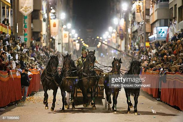 A performer from the 'Paso Blanco' rides a chariot pulled by five horses during the Holy Friday biblical parade on March 25 2016 in Lorca in Murcia...