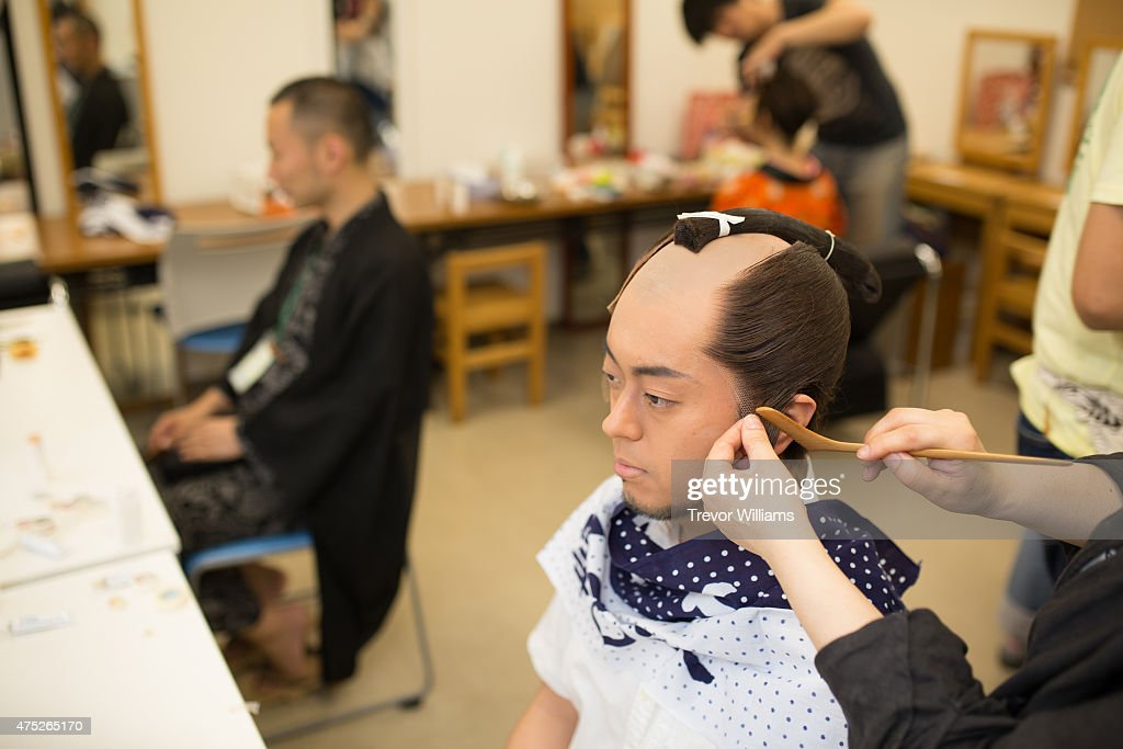 A performer getting the finishing touches done to his samurai style wig during the Uzumasa Edosakaba, an event recreating an edo-period bar at the Toei Kyoto Studio Park on May 30, 2015 in Kyoto, Japan. The Toei Kyoto Studio Park, a studio park built next to a working film set, turned itself into a big edo-period bar where people can drink and enjoy edo period culture including Japanese cuisine and samurai sword fighting.