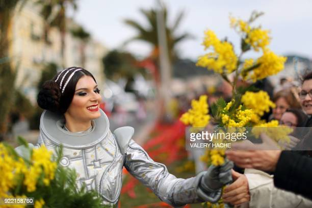 A performer hands out flowers during the 134th edition of the Nice Carnival on February 21 2018 in Nice The theme of this year's edition which runs...