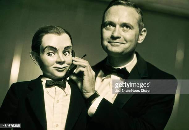 performer holding cell phone to ventriloquist dummy - ventriloquist stock photos and pictures