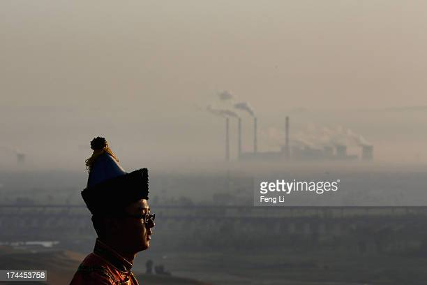 A performer in traditional costumes looks on as a power plant is seen in Xiangshawan Desert also called Sounding Sand Desert on July 19 2013 in Ordos...