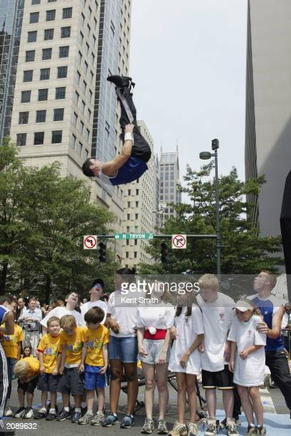 A performer jumps over children during a street party for the unveiling of the Charlotte Bobcats expansion NBA team on June 11 2003 in Charlotte...