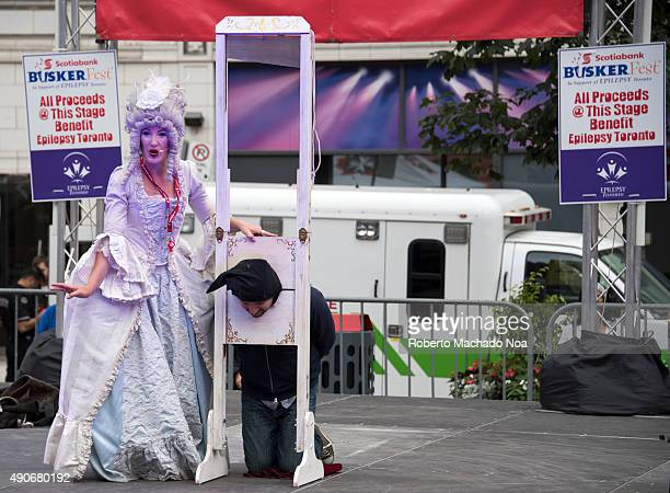 ST TORONTO ONTARIO CANADA Performer Kate Mior dressed up as Marie Antoinette doing the guillotine act at Buskerfest Toronto 2015The main purpose of...