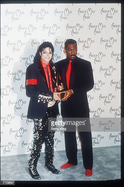 Performer Michael Jackson stands next to actor Eddie Murphy at the American Music Awards January 30 1989 in Los Angeles CA Jackson achieved...