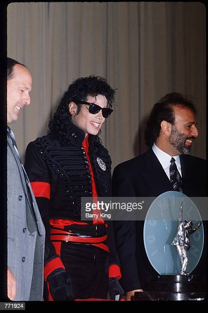 Performer Michael Jackson stands with unidentified men at an award ceremony held by CBS Records February 20 1990 in Los Angeles CA Jackson who was...