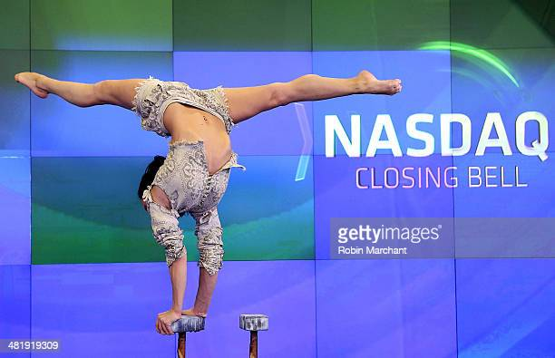 A performer of Cirque du Soleil's 'Amaluna' rings the closing bell at the NASDAQ MarketSite on April 1 2014 in New York City