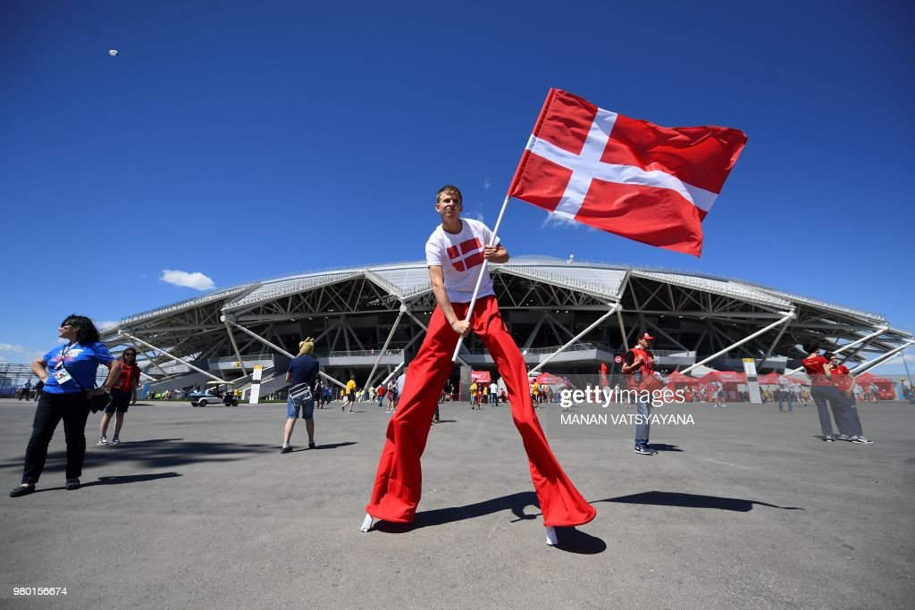 TOPSHOT - A performer on stilts waving a Danish flag poses outside the stadium ahead of the Russia 2018 World Cup Group C football match between Denmark and Australia at the Samara Arena in Samara on June 21, 2018. (Photo by MANAN VATSYAYANA / AFP) / RESTRICTED