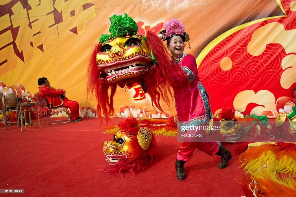 A performer poses with a 'lion' head prior to a show at a temple fair at Longtan park in Beijing on February 13, 2013. A billion-plus Asians are ushering in the lunar Year of the Snake with a week of festivities. AFP PHOTO / Ed Jones